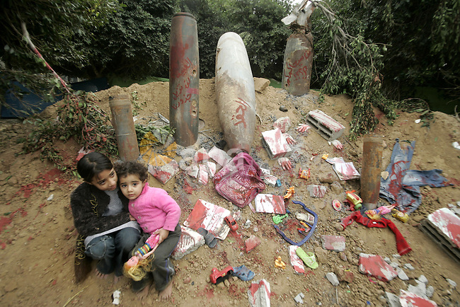 Palestinian children sit near the remains of the ammunition which was used during the war on Gaza at an exhibition organized by Hamas marks the second anniversary of Israel's three-week offensive on Gaza, in the southern Gaza Strip town of Rafah on December 29, 2010. Which more than a thousand Palestinians were killed in the Israel's war between the late 2008 and early 2009. Photo by Abed Rahim Khatib