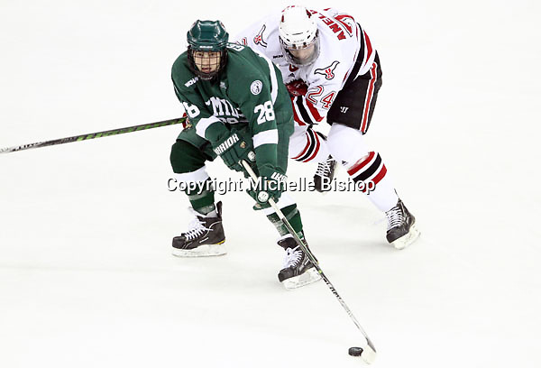 Bemidji State's Jordan George tries to control the puck while being pressured by UNO's Bryce Aneloski. Bemidji State beat UNO 4-2 Friday night during the first round of the WCHA playoffs at Qwest Center Omaha. (Photo by Michelle Bishop)