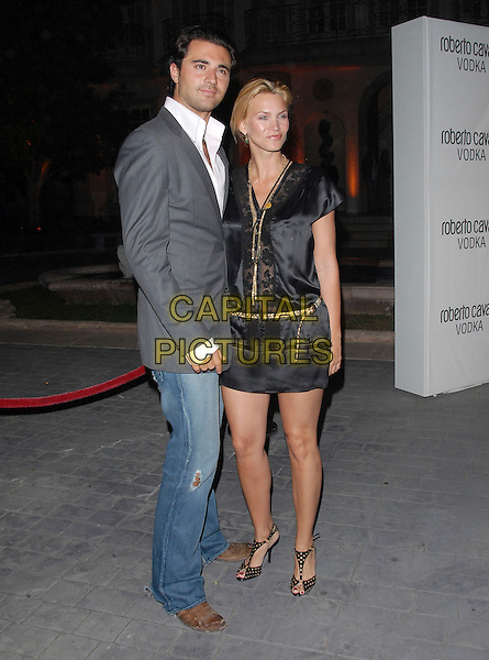 DARIUS DANESH & NATASHA HENSTRIDGE.The Launch Party for The Roberto Cavalli Vodka held at a private residence in Holmby Hills , California, USA..May 11th, 2006.Ref: DVS.full length black dress gold skirt couple grey gray denim jeans jacket.www.capitalpictures.com.sales@capitalpictures.com.Supplied By Capital PIctures