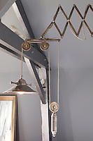 An antique wall light in front of an exposed beam painted with silver metallic paint in a child's bedroom