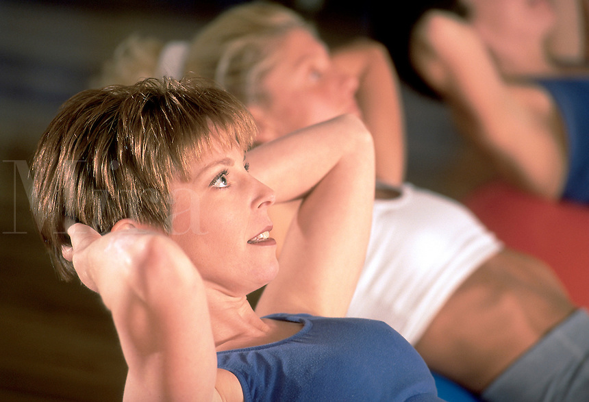 Portrait of a woman doing stomach crunches in a fitness class.