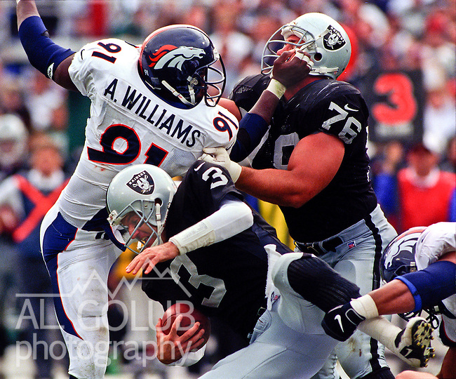 Oakland Raiders vs. Denver Broncos at Oakland Alameda County Coliseum Sunday, October 19, 1997.  Raiders beat Broncos  28-25.  Oakland Raiders guard Steve Wisniewski (76) struggles with Denver Broncos defensive end Alfred Williams (91) to protect quarterback Jeff George (3).