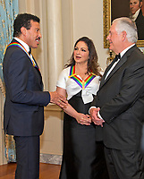 Lionel Richie, left, and Gloria Estefan, center, two of the five recipients of the 40th Annual Kennedy Center Honors speak with United States Secretary of State Rex Tillerson, right, as they wait to pose for a group photo following a dinner hosted by Secretary  Tillerson in their honor at the US Department of State in Washington, D.C. on Saturday, December 2, 2017.  The 2017 honorees are: American dancer and choreographer Carmen de Lavallade; Cuban American singer-songwriter and actress Gloria Estefan; American hip hop artist and entertainment icon LL COOL J; American television writer and producer Norman Lear; and American musician and record producer Lionel Richie. Photo Credit: Ron Sachs/CNP/AdMedia