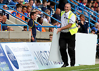 A Gillingham steward removes an advertising board after it was blown by the wind to the side of the pitch near the dug-out area during Gillingham vs Burton Albion, Sky Bet EFL League 1 Football at The Medway Priestfield Stadium on 10th August 2019