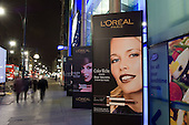 L'Oreal advertising hoardings outside Boots store on Oxford Street, central London, at night.