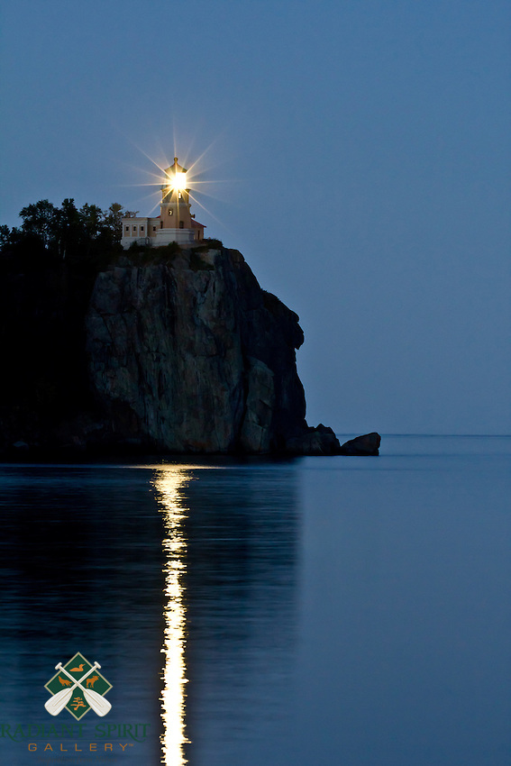 """""""Split Rock Lighthouse Illumination""""<br /> <br /> Split Rock Lighthouse illuminates Lake Superior's North Shore at twilight. The lighthouse was built following the fateful Mataafa Storm of 1905, in which 29 ships were lost. It guided ships from 1910 through 1969, at which time it was retired and added to the National Register of Historic Places. It is a rare occurrence to witness the brilliant beacon of this iconic lighthouse."""