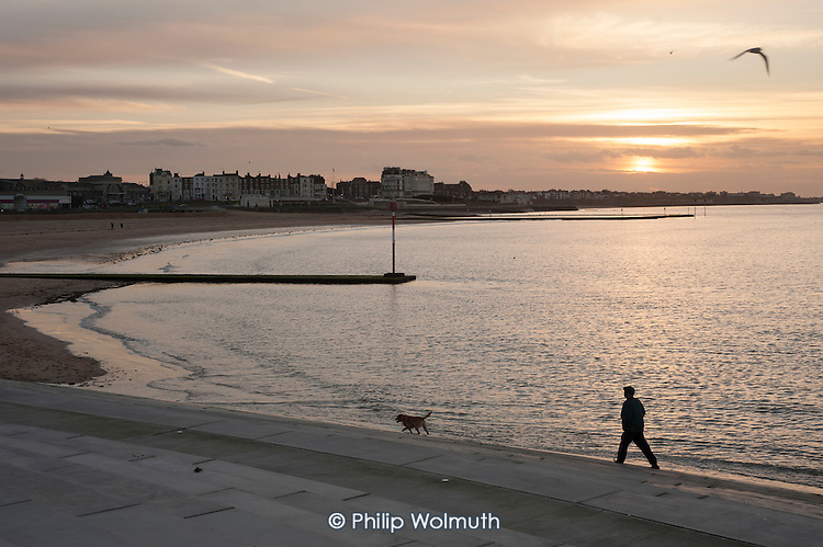 A man walking his dog on the beach, Margate, Kent.