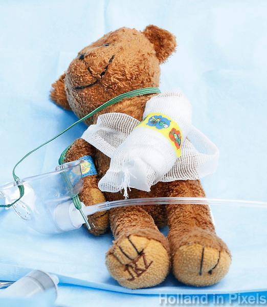 Nederland Amsterdam 2017 . Teddy Bear Hospital in het AMC ziekenhuis. Teddy Bear Hospital (TBH) is één van de grootste projecten van IFMSA-NL. Het TBH is een rollenspel. Dat houdt in dat kleuters van vier t/m zes jaar hun beer of een andere knuffel meenemen naar een nagebootst ziekenhuis. Geneeskundestudenten spelen voor arts en behandelen de knuffels. Het doel van Teddy Bear Hospital is om kinderen op een speelse manier kennis te laten maken met de gezondheidszorg, om zo de angst voor dokters en het ziek-zijn enigszins weg te nemen. Bovendien leert het medische studenten om te gaan met kinderen en trainen ze hun communicatieve vaardigheden. Tedy bear met gebroken arm op de operatietafel.  Foto Berlinda van Dam / Hollandse Hoogte