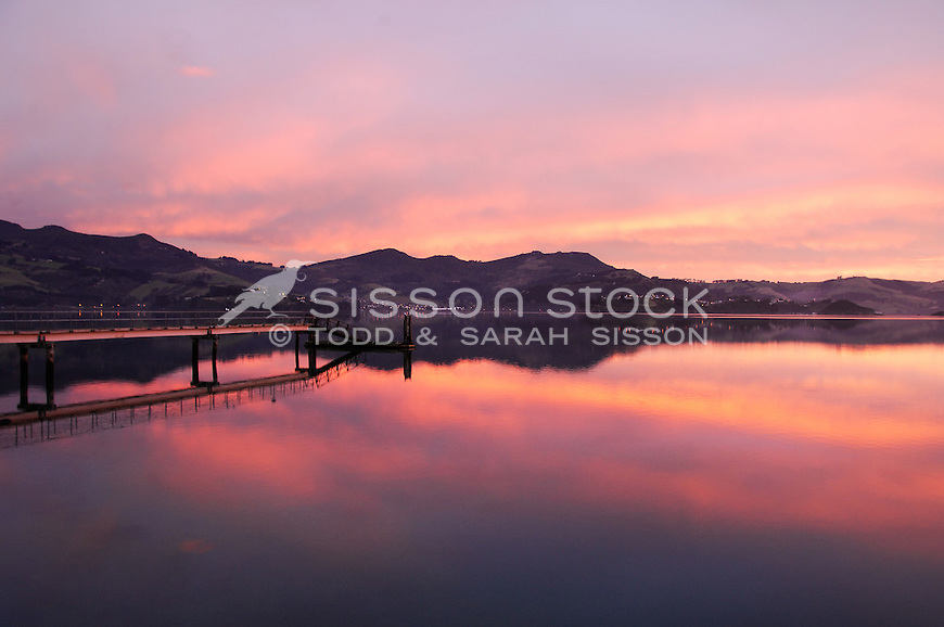 Vivid sunrise colours reflected in Otago Harbour at Broad Bay, Otago peninsula.