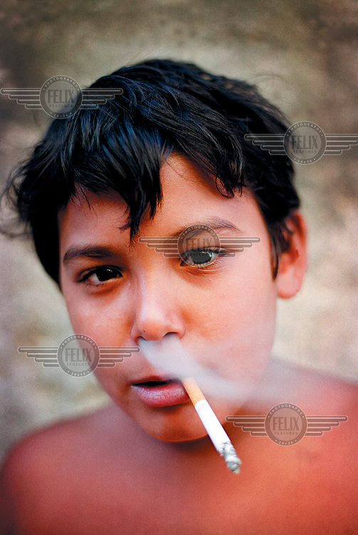 Young boy smoking a cigarette.