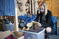 Volunteer Beckie Seba sorts shoes for sale, Friday, July 31, 2020 at Beautiful Lives Boutique in Bentonville. Volunteers from the Bentonville Discipleship group gave their time to help tag and sort clothes for the boutique. Beautiful Lives is a nonprofit that raises money to help women impacted by a variety of situations from homelessness and incarceration to international issues like sexual exploitation and trafficking. The boutique donated $4,000 in July to six local charities and four international non-profits that are working to support women said Melissa Rhodes Carter, the executive director for Beautiful Lives's three locations. All of the revenue from the boutiques minus expenses is donated to support women's causes. Check out nwaonline.com/200801Daily/ for today's photo gallery. <br /> (NWA Democrat-Gazette/Charlie Kaijo)