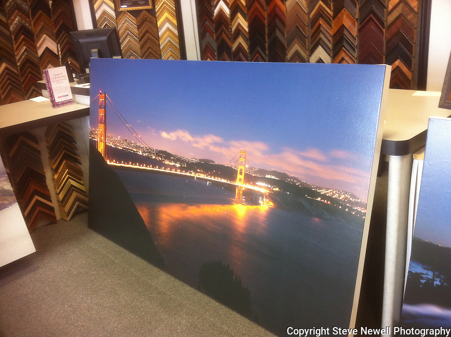 """The Night Life""  Golden Gate Bridge San Francisco, California.  A stretched canvas print at the frame shop leaning against the counter. It is a 48x84"" museum wrap. I specialize in Large Oversize Fine Art Landscapes. It is unusual for a night shot in a large print format to have such sharp detail of the Golden Gate Bridge and the City.  A few of the things I like in this photograph are: the colors of the bridge, the shadows of the cables on the Pacific Ocean, looking at the ocean you can see how the waves are moving in several different directions (something not readily visible during the day), white clouds being illuminated by the city lights and are slightly blurry showing that they were moving, the detail of all the buildings and their light in the windows, the Trans America building on the left, the Presidio on the right, the little slivers of light in the sky are airplanes in flight, stars in the sky high above the city and the cars driving over the bridge look like a laser beam of light but when you look closely you can see little bubbles of light sticking out above the main stream of light due to the cars bouncing on the suspension bridge.  I didn't realize how much the vehicles bounced until I viewed their light trails while going over the bridge. I have four different images of this scene with some of them having the vehicle light trails only being little individual lines of light that look like little snakes.  I get asked a lot about the camera settings I used to capture this image so here they are: Picture taken on June 24th, 2012 at 9:32pm, ISO 400, 30 second exposure, f13.0 aperture, with a Canon 5D Mark ll and Canon F/2.8 L series lens set at 35mm."