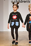 Model walks runway in an outfit from the Mon Doux Monde collection during the petitePARADE fashion show at Children's Club in the Jacob Javits Center in New York City on February 25, 2018.