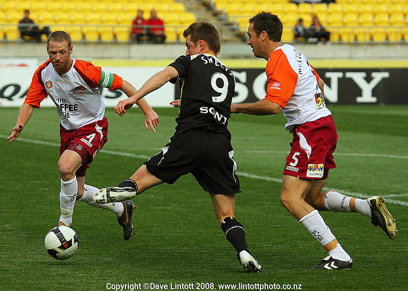Shane Smeltz tries to get a shot under pressure from Craig Moore and Joshua McLoughan in the box during the A-League football match between the Wellington Phoenix and Queensland Roar at Westpac Stadium, Wellington. Sunday, 26 October 2008. Photo: Dave Lintott / lintottphoto.co.nz