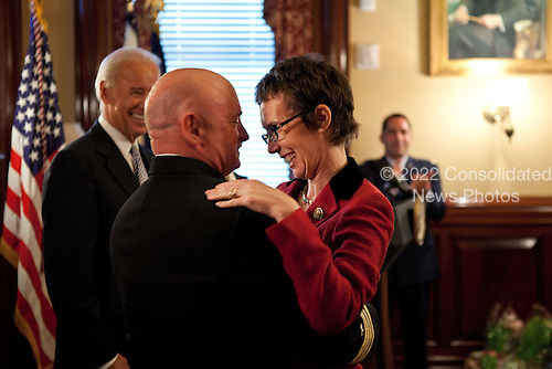 Captain Mark Kelly hugs his wife, United States Representative Gabrielle Giffords (Democrat of Arizona), after receiving the Legion of Merit from Vice President Joe Biden during a retirement ceremony in the Secretary of War Suite in the Eisenhower Executive Office Building, in Washington, D.C., October 6, 2011. .Mandatory Credit: David Lienemann - White House via CNP
