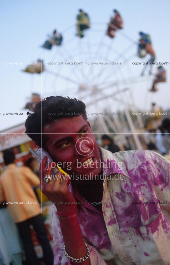 """Südasien Asien Indien IND Bombay Mumbai .indisches Fruehlingsfest Holi , Menschen bespruehen bespritzen bewerfen sich mit Farbe Farbpuder , junger Mann mit Reliance Mobiltelefon am Juhu Beach -  Fest Feste Festival Inder indisch xagndaz   .South Asia India Bombay Mumbai .indian spring festival Holi , people throw color and powder  -  man with mobile phone at Juhu Beach .  [ copyright (c) Joerg Boethling / agenda , Veroeffentlichung nur gegen Honorar und Belegexemplar an / publication only with royalties and copy to:  agenda PG   Rothestr. 66   Germany D-22765 Hamburg   ph. ++49 40 391 907 14   e-mail: boethling@agenda-fototext.de   www.agenda-fototext.de   Bank: Hamburger Sparkasse  BLZ 200 505 50  Kto. 1281 120 178   IBAN: DE96 2005 0550 1281 1201 78   BIC: """"HASPDEHH"""" ,  WEITERE MOTIVE ZU DIESEM THEMA SIND VORHANDEN!! MORE PICTURES ON THIS SUBJECT AVAILABLE!! INDIA PHOTO ARCHIVE: http://www.visualindia.net ] [#0,26,121#]"""