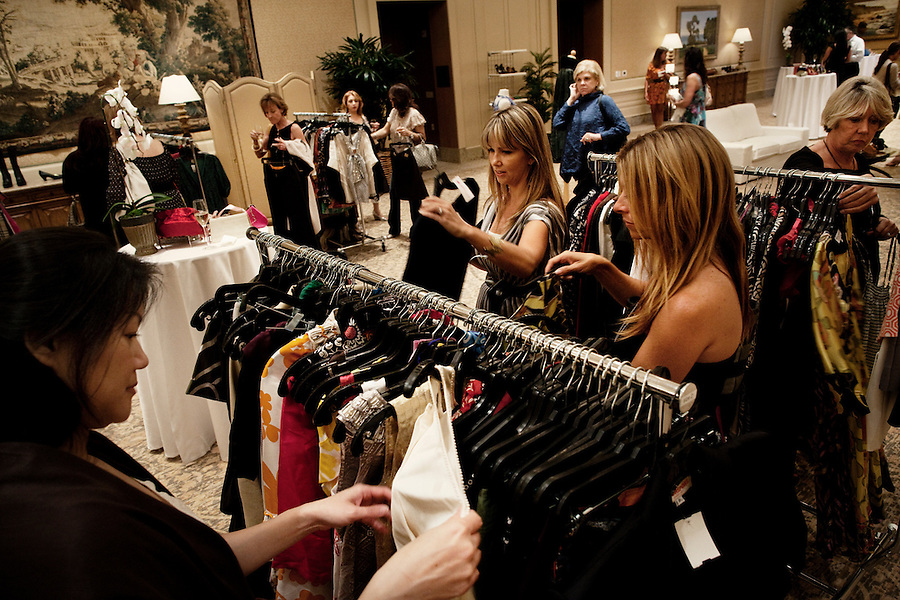 "Newport, California, July 22, 2011 - Women peruse the racks at The Divorcee Sale at the Pelican Hill Resort in Orange County. Organized by Jill Alexander, the sale offers luxury items most of which from uber-rich divorcees looking to unload their proverbial baggage. The event also donates 25 percent of its profits to breast cancer research...Alexander, who has actually never been married, started The Divorcee Sale this past spring after noticing a trend amongst her friends and colleagues going through divorces. ""Many women have an attachment to these things and they just want to move on,"" says Alexander. She added that the consignment shops were full and not really offering much in the way of sympathy in the situation. Alexander is different in that she visits the home of the divorcees, often with cakes and tissues, and acts as both a consignor and a confidant. ."