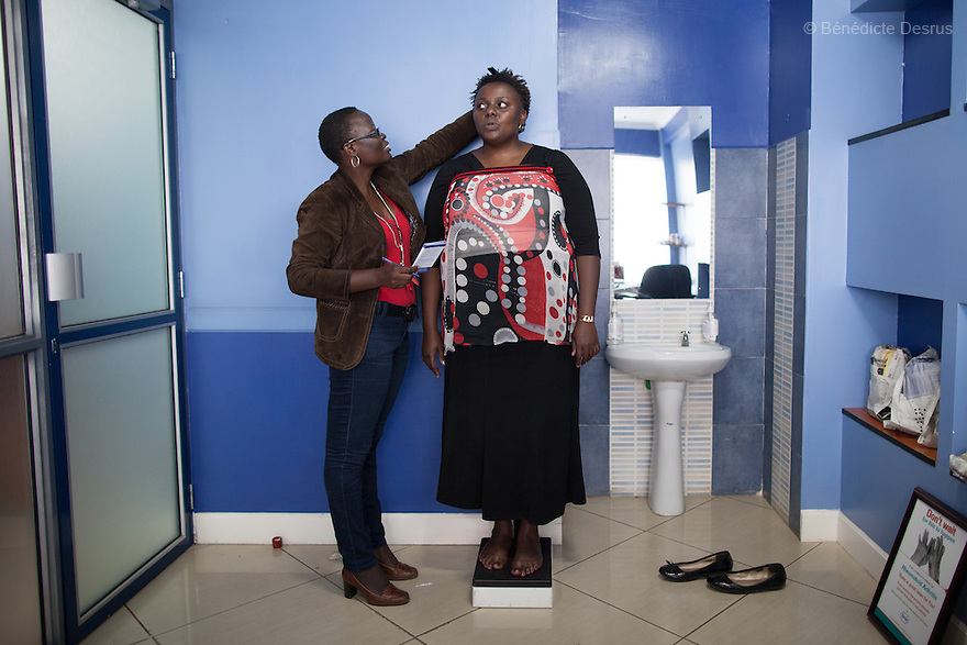 """Ruth is weighed and given a check up by AliceOjwang-Ndong, a Kenyan nutritionist and dietetic consultant during a weightloss management program in Nairobi, Kenyaon December 17, 2012. Ruth Gathu is a 35 year-old Kenyan woman who works as an office administrator. She weighs 299 pounds and weighs 175 centimeters, with a BMI of 44.3. She says: """"In Kenya, people don't spend money on nutrition programs""""…""""Obesity is in all the social class in Kenya, the rich, the middle class and the poor."""" Nairobi has a high prevalence of overweight and obesity among women, especially those in the middle and upper class. Like elsewhere in the world, the main drivers of obesity in Kenya are rapid urbanization and westernization, that have resulted in changing lifestyles such as increased consumption of """"unhealthy diets"""" and adoption of sedentary lifestyles. Photo by Bénédicte Desrus"""
