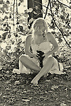 A young woman sitting cross legged wearing a white summer dress holding a red heart sitting beneath a tree in b/w