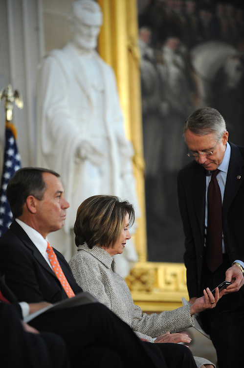 Senate Majority Leader Harry Reid, D-Nev., shows Speaker Nancy Pelosi, D-Calif., a message during a ceremony honoring the 200th birthday of Abraham Lincoln, February 12, 2009.