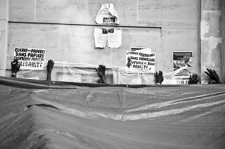 In a joint effort, workers try to colmate the space between the wall and the plastic sheet protecting their camp. The outside walls of the Bourse du Travail still carry the marks (posters, photos, drawings) of more than one year of occupation.
