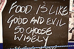 Chalkboard sign: Food is good and evil...Firostephani, Santorini, Greece.