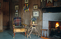 A worn leather armchair and a side table made from antlers beside the fire in this old fashioned living room