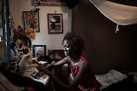 KINSHASA, DRC - JULY 17: Vanessa Nsul Kilem, age 21, does her nails in her home in Petro Congo district of Kinshasa on July 17, 2014. She dreams of becoming a super model. She has won local beauty pageants and she was one of 2000 girls casting for the thirty spots to participate in Kinshasa Fashion Week at Shark club in Kinshasa, DRC. Local and invited foreign-based designers showed their collections during the second edition of Kinshasa Fashion week. (Photo by Per-Anders Pettersson)