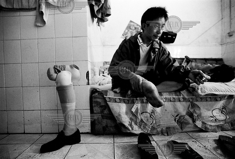 A victim and his prosthetic leg at a shelter for the victims of industrial accidents. The shelter, which houses over 30 people, is provided for by labour lawyer Zhou Litai, who uses his court earnings to finance the victums' food and lodging. .