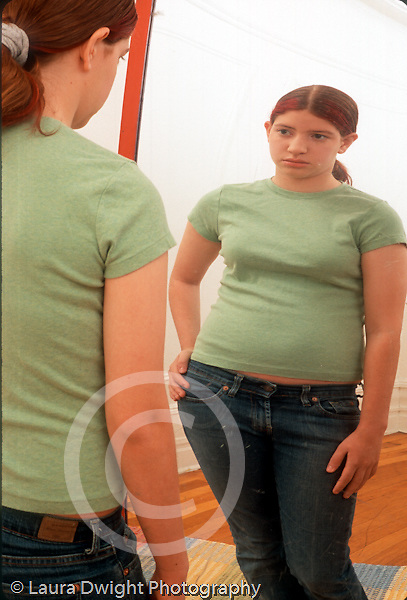 12 year old teenage girl looking at distorted reflection of herself in fun house type convex mirror vertical