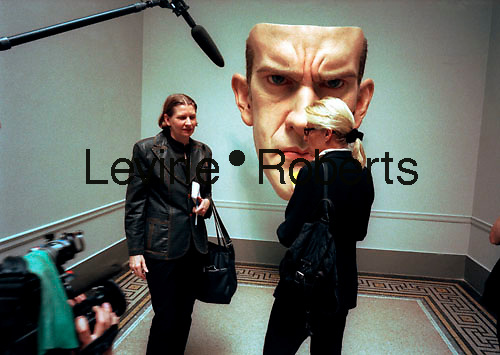 """Jeanne Moos (L), correspondent for CNN interviews a museum attendee at the opening of the """"Sensation"""" show at the Brooklyn Museum in NYC on September 30, 1999. Behind them is the sculpture """"Mask"""" 1997 by the artist Ron Mueck. (© Richard B. Levine)"""