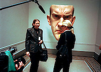 "Jeanne Moos (L), correspondent for CNN interviews a museum attendee at the opening of the ""Sensation"" show at the Brooklyn Museum in NYC on September 30, 1999. Behind them is the sculpture ""Mask"" 1997 by the artist Ron Mueck. (© Richard B. Levine)"