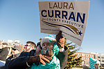 "Mineola, New York, USA. January 1, 2018. JOE CAVANAUGH, of Oceanside, is holding his young daughter EMMA CAVANAGH and a political poster ""Laura Curran for County Executive"" while standing bundled up in warm winter coats in audience during historic swearing-In of Laura Curren as Nassau County Executive, the first female County Executive, held outdoors. Temperature was a freezing 14 ℉ Fahrenheit / -10 ℃  Celsius for the outdoor ceremony held in front of Theodore Roosevelt Executive & Legislative Building."