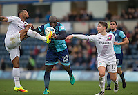 Alie Sesay of Barnet & Sam Muggleton (17) of Barnet stop Adebayo Akinfenwa of Wycombe Wanderers during the Sky Bet League 2 match between Wycombe Wanderers and Barnet at Adams Park, High Wycombe, England on 22 October 2016. Photo by Andy Rowland.