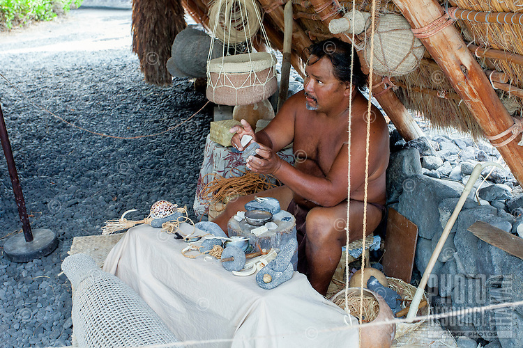 Native Hawaiian man holding artifacts while giving Hawaiian cultural lecture in Pu'uhonua o Honaunau National Historical Park, Big Island.