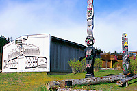 U'mista Cultural Centre and Kwakwaka'wakw (Kwakiutl) Totem Poles, Alert Bay, Cormorant Island, BC, British Columbia, Canada - Man holding Copper stands atop Dzoonokwa (Wild Woman of Woods) (left), Thunderbird sits atop Killer Whale (right)