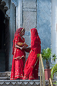 Udaipur, India. Two women in Rajasthani red saris outside the City Palace.