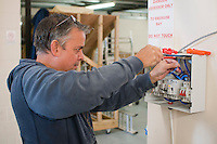 Student electrician installing a domestic fusebox, Able Skills, Dartford, Kent.