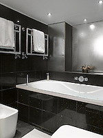 The contemporary bathroom covered with black marble tiles has a pair of chrome towel rails mounted on the wall