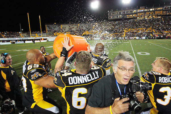 Aug 3, 2007; Hamilton, ON, CAN; Tiger-Cats tackle (69) Jonta Woodard and offensive lineman (64) Ryan Donnelly dump ice water on head coach Charlie Taaffe late in the fourth quarter against the Winnipeg Blue Bombers at Ivor Wynne Stadium. The Tiger-Cats defeated the Blue Bombers 43-22. Mandatory Credit: Ron Scheffler.