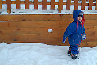 Three year old girl playing in the snow at a ski resort in the French Alps, France.