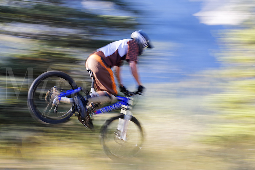 Rider performs a stoppy on mountain bike, Alberta, Canada