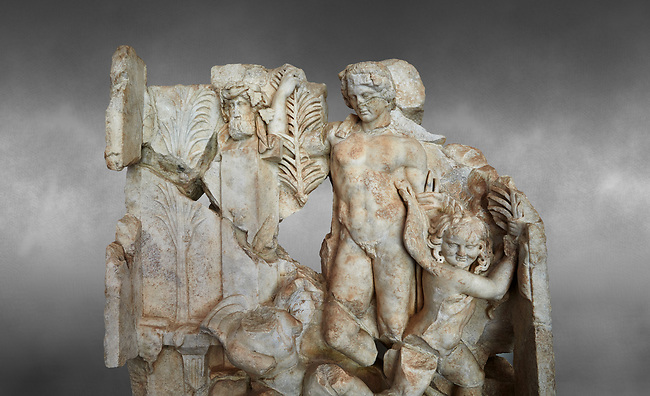 Close up of a Roman Sebasteion relief  sculpture of Agon Aphrodisias Museum, Aphrodisias, Turkey.  Against a grey background.<br /> <br /> The scene is an allegory of the athletic contest (or agon). The pillar was a beareded head of Hermes the god of the Gymnasium. Nearby is a palm of victory and a prize table with victory ribbon on it. Two winged baby Eros figures are struggling over a palm branch ( mostly broken): they act out the idea of contest, which is personified in the youthful figure behind. He hold another palm of victory: he is Agon himself.