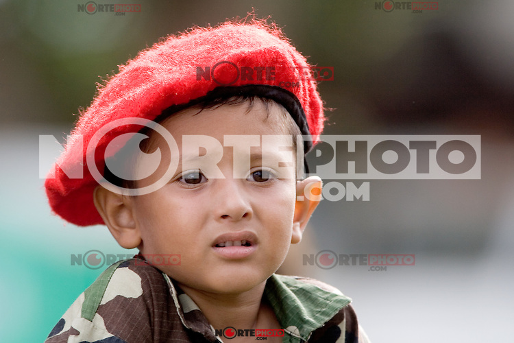"""A Venezuelan boy, wearing a version of President Hugo Chavez's trademark red beret, watches a military parade in Valencia, Venezuela, on Saturday, June 24, 2006. The military parade was to celebrate Army Day and took place in """"Campo de Carabobo"""", the field where the last big battle for the Venezuelan independence was won. (ALTERPHOTOS/Alvaro Hernandez)."""