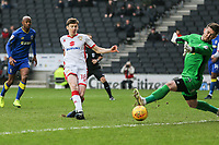 Early chance for Conor McGrandles of MK Dons (centre) is saved by the feet of Goalkeeper Joe McDonnell (right) of AFC Wimbledon during the Sky Bet League 1 match between MK Dons and AFC Wimbledon at stadium:mk, Milton Keynes, England on 13 January 2018. Photo by David Horn.