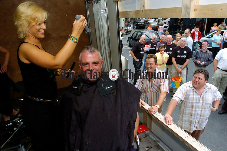 Superintendent John Kerin gets his head shaved by hairdresser Aine Keane of Top Secret  in aid of the Clare Garda Appeal Route 66 Headshave for HIV/Aids orphans in Mozambique. The close shave took place following an auction in  which two local businessmen, Tom Howard and Danny Devine, pictured at front, paid Ä2000 sponsorship for charity. Photograph by John Kelly.