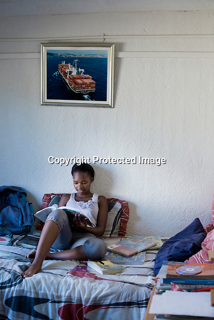 SOWETO, SOUTH AFRICA MARCH 23: A teenage girl studies sitting on her bed inside her house on March 23, 2014 in Orlando West, section of Soweto, South Africa. (Photo by: Per-Anders Pettersson)