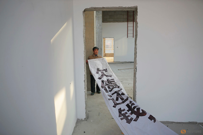 """A migrant worker shows a banner inside a building that is under construction as a part of the Zixia Garden development complex in Qianan, Tangshan City, Hebei province, China January 28, 2016. The banner, which workers claim authorities told them not to use in their protests any more, reads """"Pay back the money that you owe"""".  REUTERS/Damir Sagolj"""