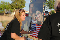 "Gilbert, Arizona – Friends and family of the Mederos Family gathered to hold a memorial for the four victims of the Gilbert Massacre occurred on May 2, 2012. According to Gilbert Police, Lisa Mederos, Amber Mederos, baby Lilly Mederos, and Jim Hiott (Amber's fiancé) were all killed by notorious white supremacist and Neo-Nazi Jason ""J.T."" Ready before taking his own life. In this image, Mistie Whiteman places an American flag below a picture of victims Lisa Mederos (bottom left picture), Amber Mederos, baby Lilly Mederos and Jim Hiott (photographed together in large picture). Photo by Eduardo Barraza © 2012"