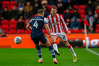 11th January 2020; Bet365 Stadium, Stoke, Staffordshire, England; English Championship Football, Stoke City versus Milwall FC; Nick Powell of Stoke City kicks the ball past Shaun Hutchinson of Millwall - Strictly Editorial Use Only. No use with unauthorized audio, video, data, fixture lists, club/league logos or 'live' services. Online in-match use limited to 120 images, no video emulation. No use in betting, games or single club/league/player publications